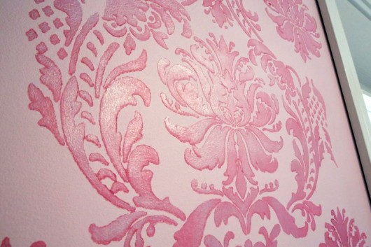Stenciling a pink and teal stenciled accent wall in a nursery using the Gabrielle Damask pattern.. http://www.cuttingedgestencils.com/damask-stencil-3.html