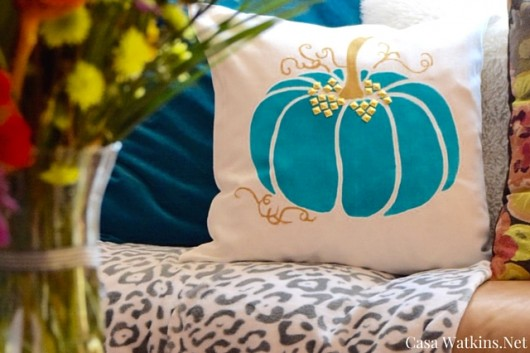 A DIY stenciled pumpkin accent pillow in teal with gold studs. http://www.cuttingedgestencils.com/pumpkin-stencils-halloween-throw-pillows-diy-home-decor.html
