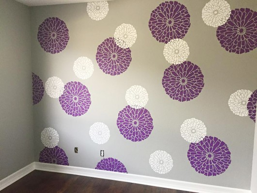 A DIY stenciled nursery accent wall in purple, gray, and white using the Summer Blossoms Flower Stencils from Cutting Edge STencils. http://www.cuttingedgestencils.com/flower-stencils-summer-blossom-floral-wall-stencil-design.html