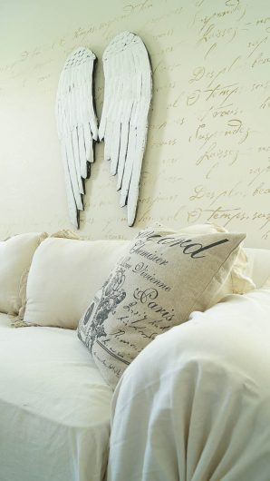 A DIY white and gold stenciled living room accent wall using the French Poem Allover Stencil from Cutting Edge Stencils. http://www.cuttingedgestencils.com/french-poem-typography-letter-stencil.html